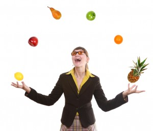 happy business woman juggling fruit on white background